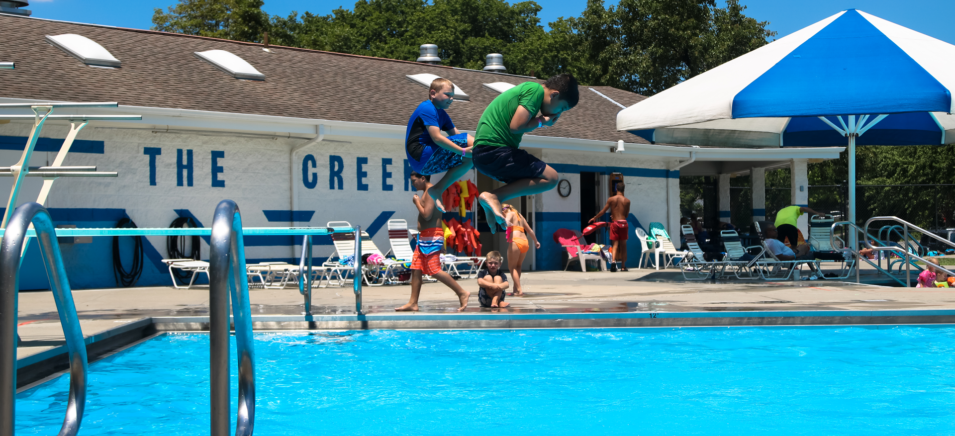 Two young boys jumping off the diving boards at Mill Creek Swimming Pool.