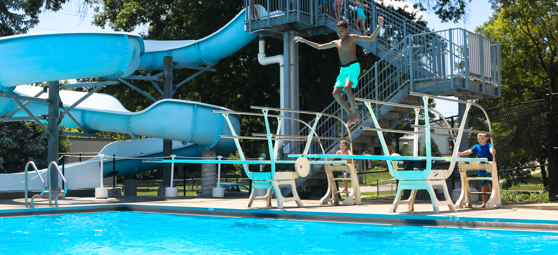 A young boy preparing to jump off the diving board at Mill Creek Swimming Pool.