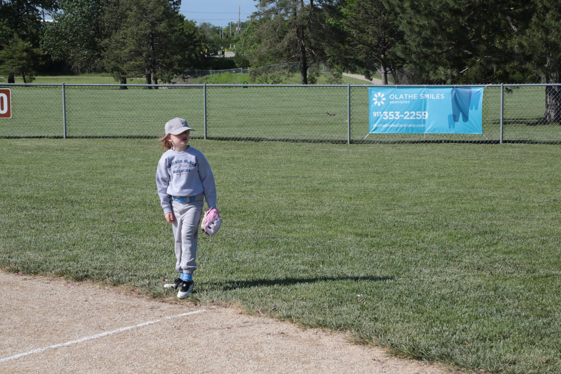 a young child is playing baseball on the infield, with the photo displaying a banner on the outfield fence