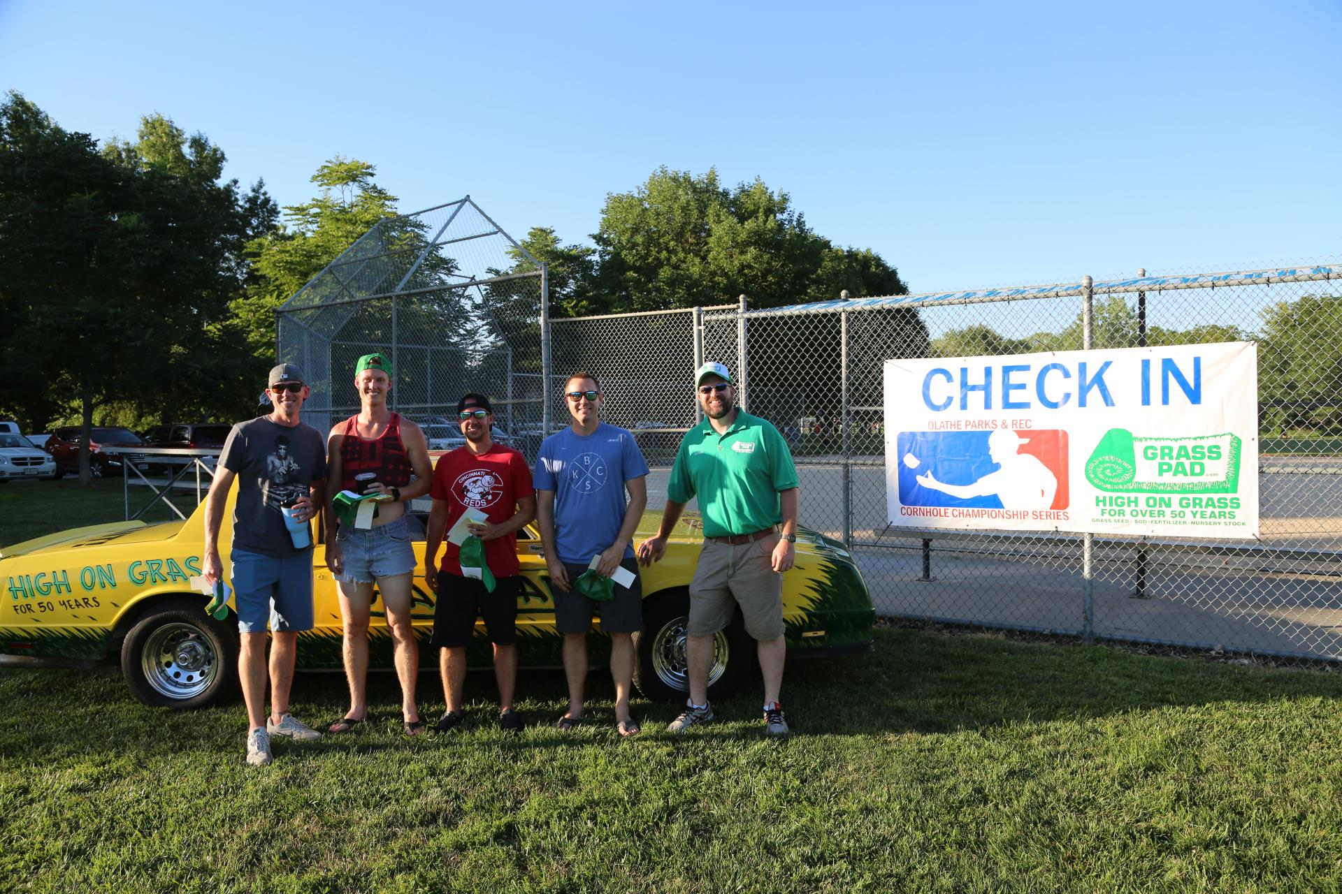 a team picture in front of the Qlathe Cornhole Championship event
